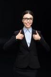 Επιχειρηματίας στο μαύρο κοστούμι που παρουσιάζει αντίχειρες που απομονώνεται επάνω στο Μαύρο Στοκ Φωτογραφία