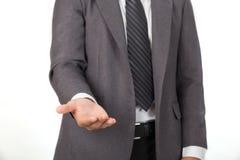 επιχειρηματίας στο περιστασιακό γκρίζο κοστούμι που δίνει ένα χέρι, μια ερώτηση ή ένα offerin Στοκ εικόνα με δικαίωμα ελεύθερης χρήσης