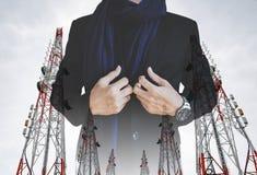 Επιχειρηματίας στο περιστασιακό κοστούμι με τους πολλαπλάσιους πύργους τηλεπικοινωνιών έκθεσης με τις κεραίες TV και το δορυφορικ Στοκ φωτογραφία με δικαίωμα ελεύθερης χρήσης