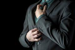 Επιχειρηματίας στο πράσινο πουκάμισο και κοστούμι που ρυθμίζει τη μαύρη γραβάτα του Στοκ εικόνες με δικαίωμα ελεύθερης χρήσης