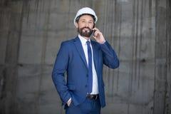 Επιχειρηματίας στο σκληρό καπέλο που μιλά στο smartphone και που χαμογελά στη κάμερα Στοκ Φωτογραφία