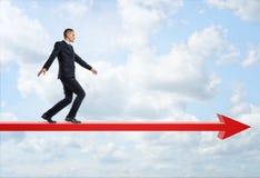 Επιχειρηματίας στο σχεδιάγραμμα που περπατά κατ' ευθείαν μπροστά το μεγάλο κόκκινο βέλος στο υπόβαθρο του μπλε ουρανού Στοκ Φωτογραφίες