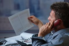 Επιχειρηματίας στο τηλέφωνο που ελέγχει το έγγραφο Στοκ Εικόνες