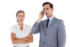 Επιχειρηματίας στο τηλέφωνο δίπλα στο συνάδελφό του Στοκ φωτογραφίες με δικαίωμα ελεύθερης χρήσης