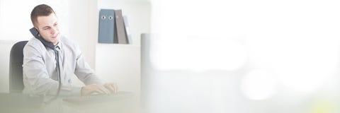Επιχειρηματίας στο τηλέφωνο δακτυλογραφώντας στον υπολογιστή Στοκ φωτογραφία με δικαίωμα ελεύθερης χρήσης