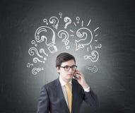 Επιχειρηματίας στο τηλέφωνο, ερωτηματικά Στοκ Εικόνες