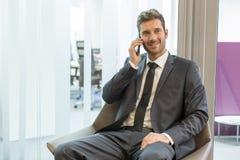 Επιχειρηματίας στο τηλέφωνο κυττάρων που κάθεται στο σαλόνι Στοκ εικόνα με δικαίωμα ελεύθερης χρήσης