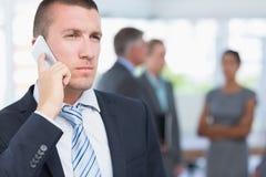 Επιχειρηματίας στο τηλέφωνο με τους συναδέλφους πίσω από τον Στοκ Φωτογραφία