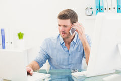 Επιχειρηματίας στο τηλέφωνο που χρησιμοποιεί το lap-top του στο γραφείο Στοκ εικόνα με δικαίωμα ελεύθερης χρήσης