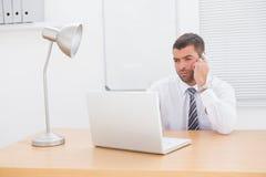 Επιχειρηματίας στο τηλέφωνο που χρησιμοποιεί το lap-top του στο γραφείο Στοκ φωτογραφίες με δικαίωμα ελεύθερης χρήσης