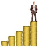 Επιχειρηματίας στο χρυσό σωρό νομισμάτων Στοκ Εικόνες