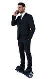 Επιχειρηματίας στο hoverboard που μιλά στο κινητό τηλέφωνο Στοκ Φωτογραφία