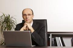 Επιχειρηματίας στο lap-top στην αρχή στοκ φωτογραφίες
