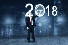 Επιχειρηματίας σχετικά με ένα κουμπί έναρξης με τους αριθμούς 2018 Στοκ Φωτογραφίες