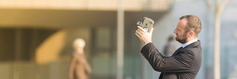 Επιχειρηματίας υπαίθριος με μια εκλεκτής ποιότητας κάμερα ταινιών Στοκ φωτογραφία με δικαίωμα ελεύθερης χρήσης