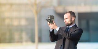 Επιχειρηματίας υπαίθριος με μια εκλεκτής ποιότητας κάμερα ταινιών Στοκ Φωτογραφίες