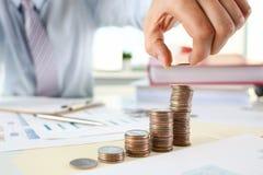 Επιχειρηματίας χεριών που βάζει τα χρήματα καρφιτσών στοκ εικόνες