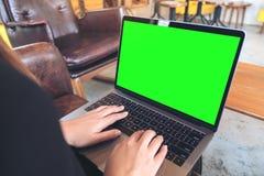 Επιχειρηματίας χρησιμοποιώντας και δακτυλογραφώντας στο lap-top με την κενή πράσινη οθόνη υπολογιστών γραφείου στον ξύλινο πίνακα Στοκ εικόνες με δικαίωμα ελεύθερης χρήσης