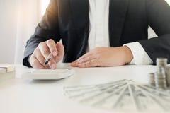 Επιχειρηματίας χρησιμοποιώντας τον υπολογιστή για τα κεφάλαια σχεδίων επένδυσης και καταθέτοντας την έννοια σε τράπεζα στοκ φωτογραφίες