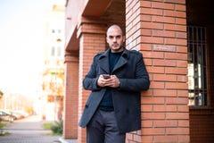 Επιχειρηματίας χρησιμοποιώντας το κινητό τηλέφωνο και κλίνοντας στον τοίχο οδών Στοκ εικόνες με δικαίωμα ελεύθερης χρήσης