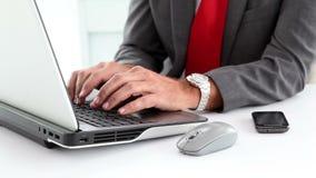 Επιχειρηματίας χρησιμοποιώντας το lap-top και δακτυλογραφώντας στο τηλέφωνό του απόθεμα βίντεο