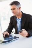 Επιχειρηματίας χρησιμοποιώντας το lap-top και κρατώντας το smartphone Στοκ φωτογραφία με δικαίωμα ελεύθερης χρήσης