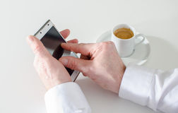 Επιχειρηματίας χρησιμοποιώντας το smartphone και πίνοντας έναν καφέ Στοκ εικόνα με δικαίωμα ελεύθερης χρήσης