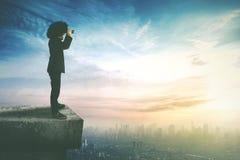 Επιχειρηματίας Afro που χρησιμοποιεί έναν διοφθαλμικό στη στέγη Στοκ Εικόνα