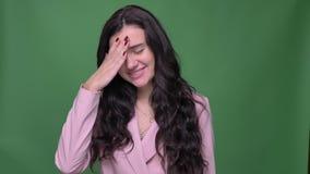 Επιχειρηματίας Brunette στις ρόδινες χειρονομίες σακακιών facepalm για να παρουσιάσει την ενόχληση και ενόχληση στο πράσινο υπόβα απόθεμα βίντεο