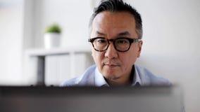 Επιχειρηματίας eyeglasses με το lap-top στο γραφείο απόθεμα βίντεο