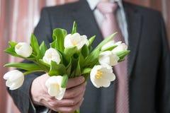 Επιχειρηματίας gves μια ανθοδέσμη των λουλουδιών Στοκ Εικόνες