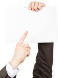 Επιχειρηματίας pointimg στο μικρό κενό έγγραφο Στοκ Φωτογραφία