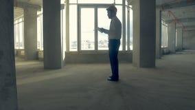 Επιχειρηματίας, realtor, επενδυτής στο σκληρό καπέλο που περπατά στο ατελές κτήριο Ουρανοξύστης μέσα κάτω από την κατασκευή φιλμ μικρού μήκους