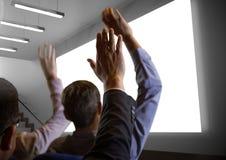 Επιχειρηματίες με τα χέρια που αυξάνονται επάνω μπροστά από την οθόνη διασκέψεων Στοκ εικόνες με δικαίωμα ελεύθερης χρήσης