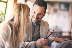 Επιχειρηματίες με την ταμπλέτα που μιλά στον ηλιόλουστο καφέ στοκ φωτογραφία