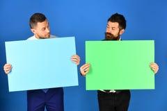 Επιχειρηματίες με τους περίεργους πίνακες σημαδιών προσώπων παρόντες πράσινους και ρόδινους Στοκ εικόνες με δικαίωμα ελεύθερης χρήσης