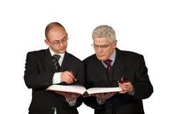 Επιχειρηματίες με τους σωλήνες που διαβάζουν ένα βιβλίο στοκ εικόνες
