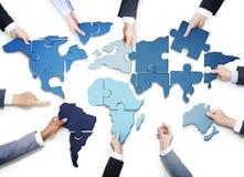 Επιχειρηματίες με το τορνευτικό πριόνι που διαμορφώνει τον παγκόσμιο χάρτη Στοκ Φωτογραφία