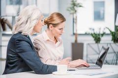 Επιχειρηματίες με το lap-top που συζητούν το επιχειρησιακό πρόγραμμα για τη συνάντηση στην αρχή Στοκ εικόνα με δικαίωμα ελεύθερης χρήσης