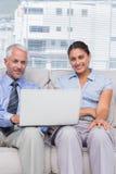 Επιχειρηματίες με το lap-top που χαμογελούν στη συνεδρίαση καμερών στον καναπέ Στοκ φωτογραφίες με δικαίωμα ελεύθερης χρήσης