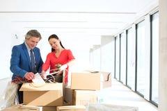 Επιχειρηματίες που ανοίγουν τα κουτιά από χαρτόνι στο νέο γραφείο Στοκ φωτογραφία με δικαίωμα ελεύθερης χρήσης