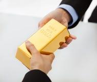 Επιχειρηματίες που ανταλλάσσουν τη χρυσή ράβδο στοκ φωτογραφία