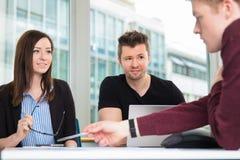 Επιχειρηματίες που εξετάζουν την εξήγηση συναδέλφων στο γραφείο Στοκ εικόνα με δικαίωμα ελεύθερης χρήσης