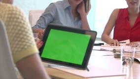 Επιχειρηματίες που εξετάζουν την ψηφιακή ταμπλέτα με την πράσινη οθόνη απόθεμα βίντεο