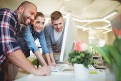 Επιχειρηματίες που εξετάζουν τον υπολογιστή στην αρχή στοκ εικόνες