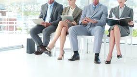 Επιχειρηματίες που εξετάζουν το σημειωματάριο και το smartphone απόθεμα βίντεο