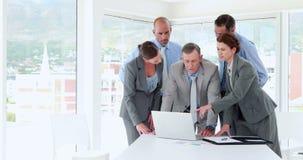 Επιχειρηματίες που εξετάζουν το φορητό προσωπικό υπολογιστή κατά τη διάρκεια της συνεδρίασης φιλμ μικρού μήκους