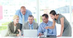 Επιχειρηματίες που εξετάζουν το φορητό προσωπικό υπολογιστή κατά τη διάρκεια της συνεδρίασης απόθεμα βίντεο