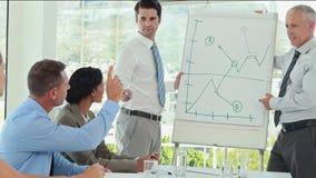 Επιχειρηματίες που εξηγούν τη γραφική παράσταση στο whiteboard απόθεμα βίντεο
