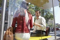Επιχειρηματίες που επικοινωνούν στη στάση λεωφορείου Στοκ φωτογραφία με δικαίωμα ελεύθερης χρήσης